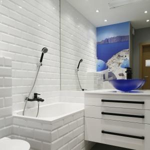 W tej łazience dobrze wykorzystano białe cegiełki w połączeniu z lustrem i białymi szafkami. Wszystko to nadało wnętrzu dużo przestronności i jasności. Projekt: Ewa Para. Fot. Bartosz Jarosz.