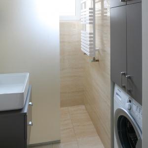 Matowe szkło zostało wykorzystane do oddzielenia strefy prysznicowej od pozostałej części łazienki. W malutkiej łazience wygospodarowano także miejsce na pralkę i pojemną szafę tuż nad nią. Projekt: Katarzyna Karpińska-Piechowska. Fot. Bartosz Jarosz.