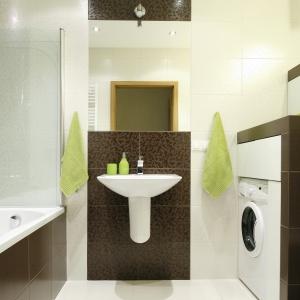 Brązowe płytki zostały podkreślone bielą ścian i podłogi. Ciekawymi dodatkami ożywiającymi wnętrze są ręczniki i dozownik mydła w kolorze zielonym. Projekt: Marta Kilan. Fot. Bartosz Jarosz.