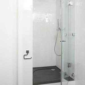 Do bieli ścian i błękitu umywalek dodano kontrastującą ciemnoszarą podłogę, a jej kontynuacją jest podwyższenie brodzika prysznica w tym samym kolorze. Rozwiązaniem oszczędzającym przestrzeń jest montaż prysznica we wnęce, którą oddzielają od reszty szklane drzwi kabiny. Projekt: Katarzyna Uszok. Fot. Bartosz Jarosz.