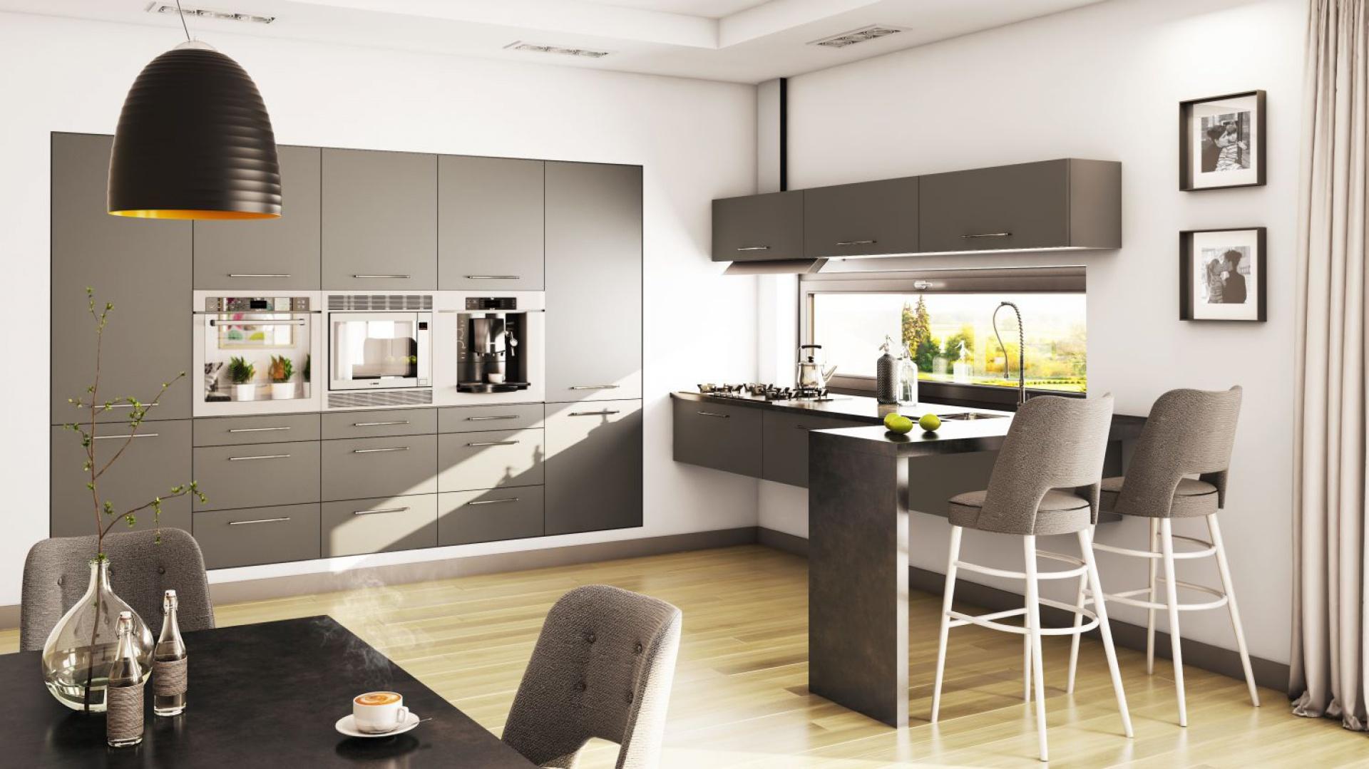 W tej kuchni wszystko jest szare - również wysoka zabudowa, która swoimi matowymi frontami kontrastuje z białą ścianą, w której wnękę została wpisana. Fot. Moelke Kuchnie, kuchnia Moelkepunto Grafit.