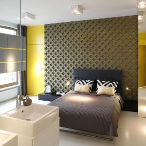 Ściana wykończona betonowymi płytami, tj. układa się podjazdy, to kontrowersyjne rozwiązanie. Wnętrze dodatkowo ożywia żółty kolor wydobywający się spod geometrycznych elementów. Projekt: Monika i Adam Bronikowcy. Fot. Bartosz Jarosz.