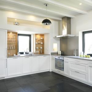 Zabudowa białej kuchni ma kształt litery L. Nie ma w niej górnych szafek, a jedynie dekoracyjne półki przy oknie. Froty mebli są delikatnie zdobione rzeźbieniami. Projekt: Kamila Paszkiewicz. Fot. Bartosz Jarosz.
