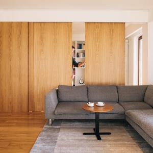 Gabinet schowano w przestrzeni za salonem, w jednej linii z pokojem dziennym. Można otworzyć go na przestrzeń wypoczynku lub przesłonić przesuwnymi, ruchomymi drzwiami. Projekt: 81.WAW.PL. Fot. Rafał Kłos.