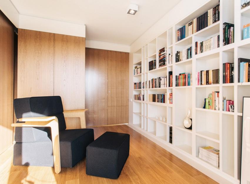 Nowoczesne mieszkanie urządzono w stylu minimalistycznym. Oszczędność w doborze dodatków i ekonomia projektu sprawiły, że udało się wygospodarować oddzielne pomieszczenie na gabinet z pojemną biblioteczką. Projekt: 81.WAW.PL. Fot. Rafał Kłos.