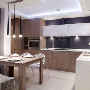 W tej kuchni ściany wykończono fioletową tapetą z subtelnym, pionowym tłoczeniem. Nad blatem osłonięto ją taflą przeźroczystego szkła. Projekt i zdjęcia: Małgorzata Brewczyńska.