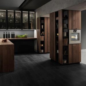 Model Vogue to piękna, elegancka kuchnia zaprojektowana specjalnie z myślą o otwartych strefach dziennych. Elementem mającym integrować kuchnię z salonem są wysokie szafki z licznymi otwartymi półkami. Fronty pomalowano matowym, grafitowym lakierem oraz wykończono naturalnym fornirem orzechu Canletto. Projekt: MaMa Studio. Fot. Binova, model Vogue.