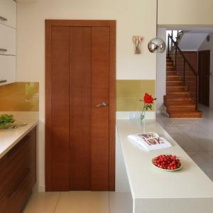 W tej kuchni urządzonej w mieszance bieli i brązów cegła ma delikatny kolor, co sprawia, że idealnie harmonizuje z drewnianymi elementami. Projekt: Magdalena Bonin-Jarkiewicz. Fot. Bartosz Jarosz.
