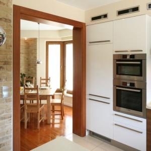 Cegłą wykończono ścianę, prowadzącą z kuchni do jadalni. Tam również na ścianie można zobaczyć identyczną cegłę - stała się ona elementem spajającym pomieszczenia. Projekt: Magdalena Bonin-Jarkiewicz. Fot. Bartosz Jarosz.