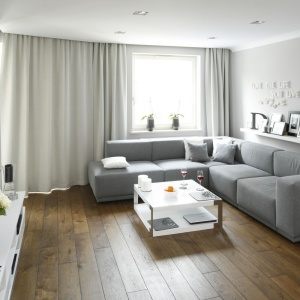 Salon urządzono w stonowanych szarościach. Szara sofa jest ozdobą wnętrza utrzymanego w nowoczesnym stylu. W zestawieniu z miękkimi zasłonami tworzy jednak ciepłą i przyjazną kompozycję. Projekt: Karolina Łuczyńska. Fot. Bartosz Jarosz.