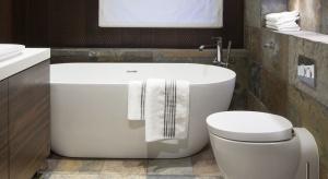 W tej eleganckiej, niewielkiej łazience szafki sięgają do sufitu. Zamiast płytek ceramicznych, na ścianach i podłodze jest naturalny łupek.