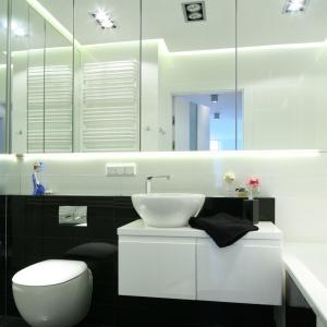 Na ścianie na wprost wejścia do łazienki zewiszono szafki lustrzane. Nad i pod nimi są zainstalowane taśmy oświetleniowe LED. Umywalka to elegancki model nablatowy. Fot. Bartosz Jarosz.