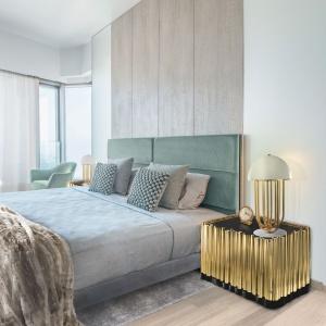 Ścianę za łóżkiem wykończono drewnem na całej wysokości. Nieco chłodne w wyrazie wnętrze nabrało dzięki temu ciepła i intymności. Fot. Boca do Lobo.