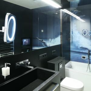Duże lustro optycznie powiększa niewielką łazienkę i ciekawie eksponuje fototapetę z pływakiem. Wanna została wyposażona w szklany panel prysznicowy. Fot. Bartosz Jarosz.