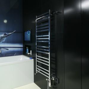 Nad wanną: wodoodporny telewizor. W ścianie obok grzejnika jest ukryty duży schowek. Jego drzwi z płyty MDF wtapiają się w czarne tło z granitu. Fot. Bartosz Jarosz.