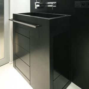 Umywalka i korpus szafki to czarny granit, zaś fronty szuflad – płyta MDF. Wykonano je pod wymiar wąskiego narożnika przy drzwiach. Fot. Bartosz Jarosz.