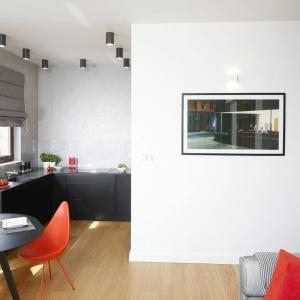 Kuchnia otwarta na salon daje wiele swobody jej użytkownikom. Brak górnej zabudowy optycznie powiększa przestrzeń, zaś czarne meble połączone zotynkowaną ścianą, przypominającą wwyglądzie beton nawiązują do stylu industrialnego. Projekt: Małgorzata Łyszczarz. Fot. Bartosz Jarosz.