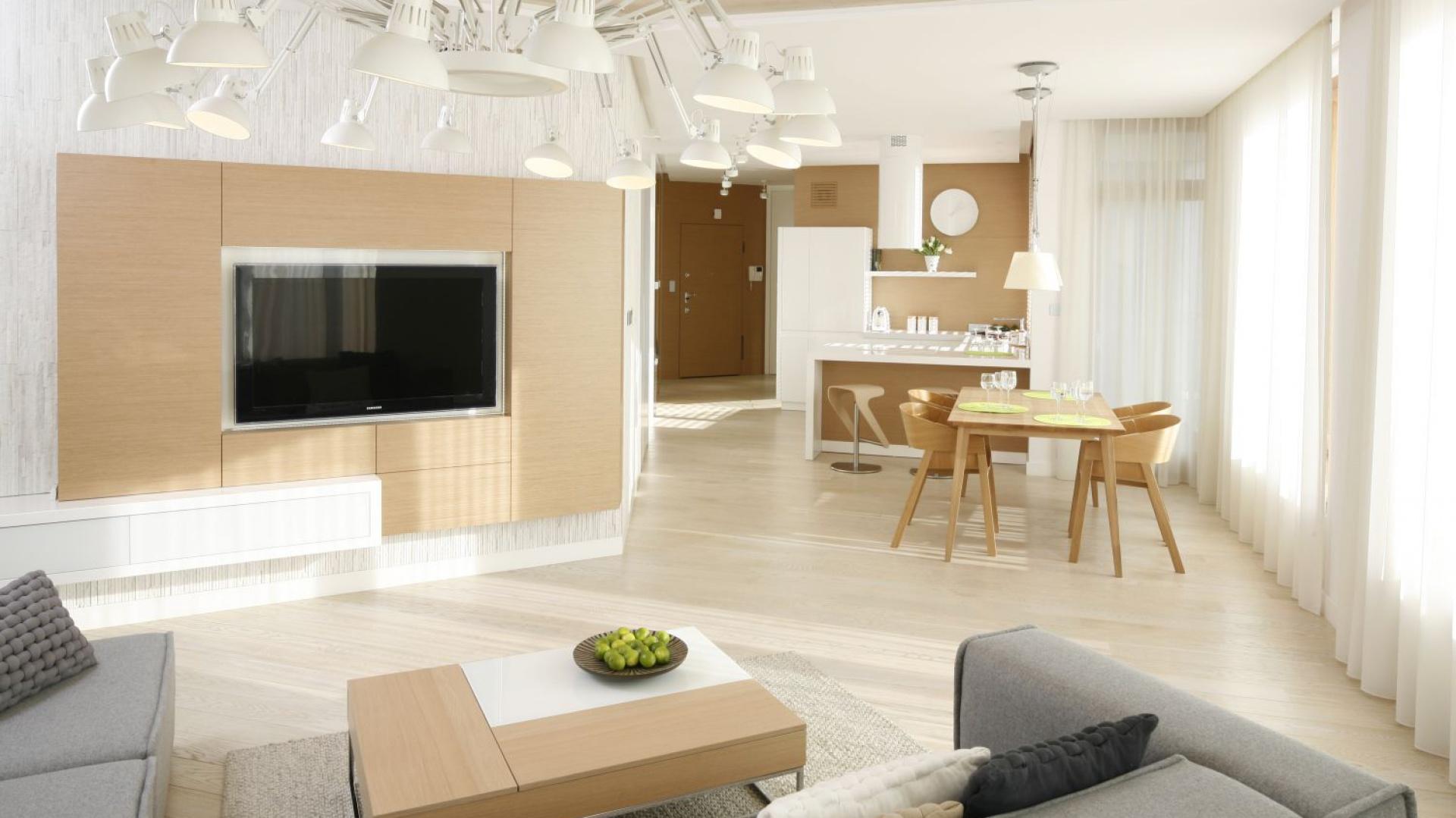 W przestronnym salonie telewizor zawieszono na ścianie z zabudową wykonaną z jasnego drewna dębowego. Projekt: Maciej Brzostek. Fot. Bartosz Jarosz.