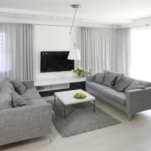 W eleganckim salonie dominują szarości. Telewizor zawieszony na ścianie można oglądać siedząc na jednej z dwóch kanap.Projekt: Karolina Stanke-Szadujko, Łukasz Szadujko. Fot. Bartosz Jarosz.