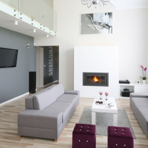 W otwartym na dwie kondygnacje salonie znalazło się wystarczająco dużo miejsca na elegancki kominek, jak i ścianę z telewizorem. Tę ostatnią stylistycznie wyróżniono szarym kolorem, w którym są także kanapy. Projekt: Karolina i Artur Urban. Fot. Bartosz Jarosz.