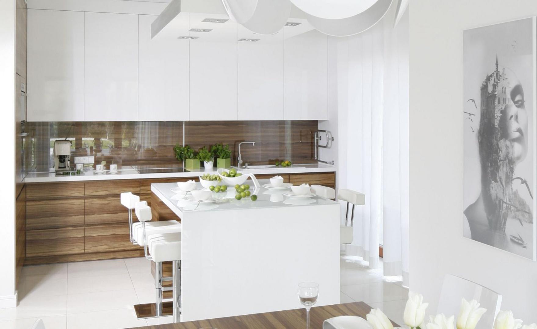 Elegancka kuchnia, w której piękny stonowany kolor drewna zestawiono z bielą. Obie wersje frontów wykończono w wysokim połysku. Projekt: Agnieszka Ludwinowska. Fot. Bartosz Jarosz.