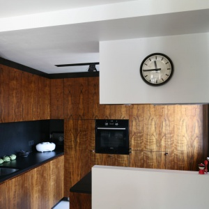 Efektowna kuchnia urządzona w stylu amerykańskiego minimalizmu lat 50-tych. Fronty zabudowy kuchennej wykończono fornirem w ciepłym wybarwieniu, a blat i ścianę nad blatem utrzymano w czerni. Projekt: Kasia i Michał Dudko. Fot. Bartosz Jarosz.