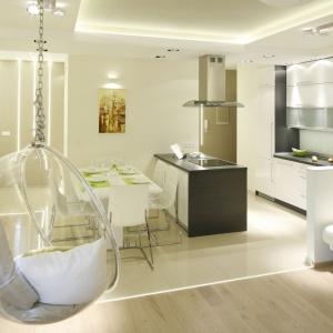To jednak nie wyspa jest elementem wyznaczającym granicę pomiędzy kuchnią a salonem a biały pas pomiędzy różnymi posadzkami na podłodze oraz niewielka półścianka zamykająca kuchnię od strony salonu. Projekt: Marta Kilan. Fot. Bartosz Jarosz.