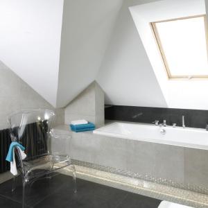 Wzrok w łazience przyciąga przezroczyste, eleganckie krzesło, dodające przestrzeni pod skosami lekkiego wyrazu. Projekt: Marta Kilan. Fot. Bartosz Jarosz.