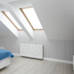 W sypialni wzrok przyciąga grzejnik płytowy z delikatnym dekoracyjnym tłoczeniem na froncie. Projekt: Marta Kilan. Fot. Bartosz Jarosz.