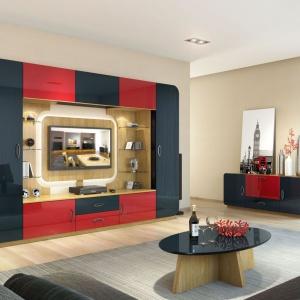 Oki marki Mebin to wieloelementowa meblościanka o nieco futurystycznym wzornictwie. Kompozycja jasnych elementów tworzy ciekawy efekt optyczny – pomiędzy narożnikami ze szklanymi półeczkami a panelem TV powstaje przestrzeń, przez którą widoczna jest ściana. Fot. Mebin.