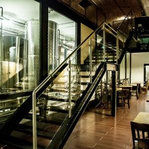 """Właściciele restauracji Browar Lubicz wyeksponowali piwnice z tradycyjnym kolebkowym sklepieniem, umieszczając tu część produkcyjną browaru za szybą tak, aby goście mogli praktycznie""""dotknąć"""" tanków z trunkiem. Fot. Dawid Dobroń."""