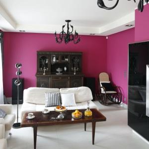 Kolor fuksji całkowicie zdominował salon. Stanowi on wyraziste tło dla stylowych mebli i czarnych dodatków. Projekt: Beata Ignasiak. Fot. Bartosz Jarosz.