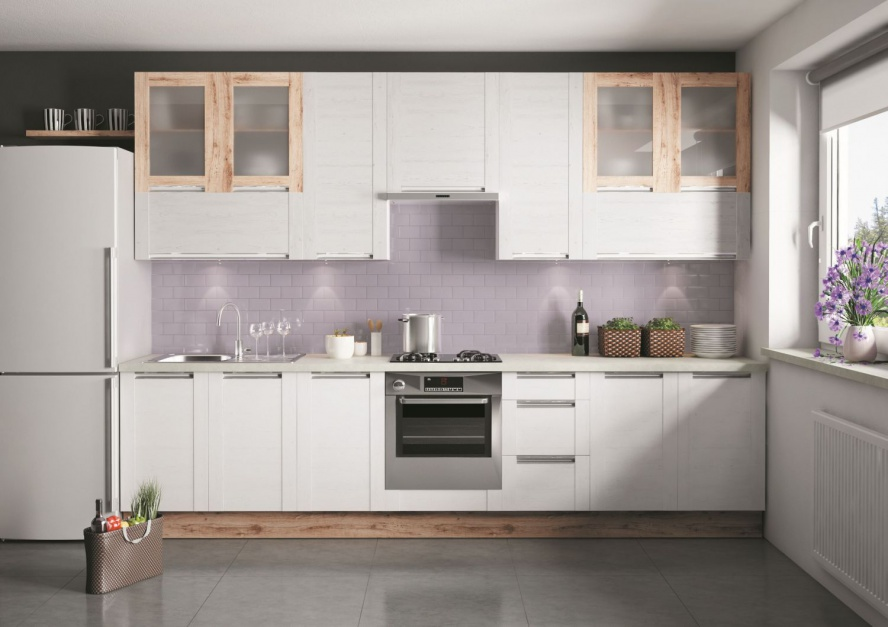 Białe fronty delikatnie ocieplone ramami w drewnianym dekorze wokół matowych przeszkleń sprawiają, że ta kuchnia nabiera skandynawskiego charakteru. W drewnianym dekorze są również cokoły. Fot. KAM Kuchnie, model Olivia.