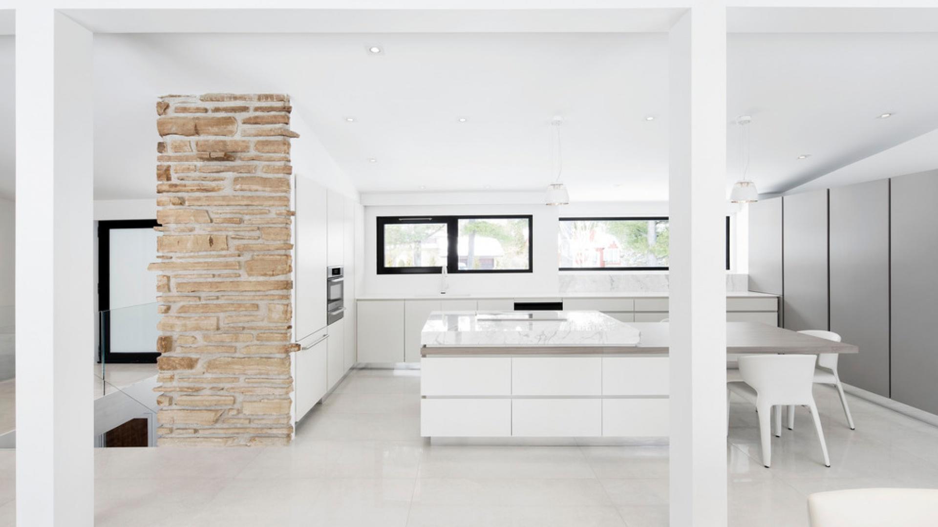 Dominującą we wnętrzu niemal sterylną biel przełamują i ocieplają naturalne materiały, np. naturalny kamień. Projekt: Architecture Open Form. Fot. Adrien Williams.