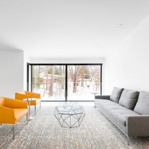 Przez mieszkanie przewijają się geometryczne motywy. W kąciku wypoczynkowym jest to metalowy, ażurowy stolik kawowy. Projekt: Architecture Open Form. Fot. Adrien Williams.