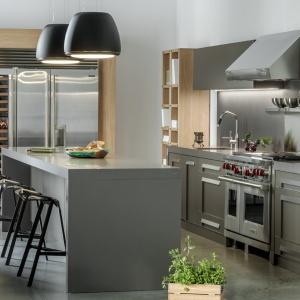 Aranżacja kuchni w stylu amerykańskim. Delikatnie frezowane fronty zdobi grafitowy lakier, a z całością harmonizują stalowe sprzęty AGD i czarne industrialne lampy. Fot. Zajc Kuchnie, kuchnia NY.