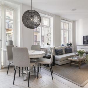 W małym wnętrzu znalazło się miejsce na kącik jadalniany z okragłym stołem i eleganckimi beżowymi krzesłami. Całości dopełnia nowoczesny żyrandol. Fot. SvenskFast.se