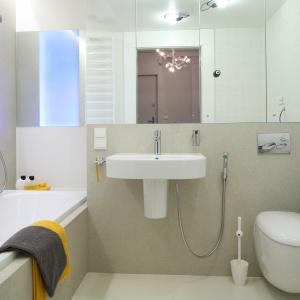 Łazienka jest jasna. Wizualnie powiększają lustra szafki nad umywalką. Fot. Bartosz Jarosz.