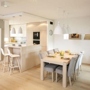 Zarówno nad stołem jadalnianym, jak i wyspą kuchenną zawisły białe lampy, których powierzchnia idealnie harmonizuje z frontami górnych szafek w kuchni. Projekt: Małgorzata Galewska. Fot. Bartosz Jarosz.