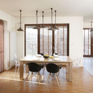 Całe mieszkanie urządzono w modnym stylu loft, nie inaczej postąpiono również z jadalnią. Industrialny charakter przestrzeni spożywania posiłków nadają metalowe klosze i łańcuchy, na których zawisły. Projekt: Marta Kruk. Fot. Bartosz Jarosz.
