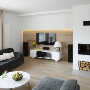 Biały kominek z dwom schowkami na drewno zamontowano tuż przy ścianie z telewizorem. Projekt: Małgorzata Galewska. Fot. Bartosz Jarosz.