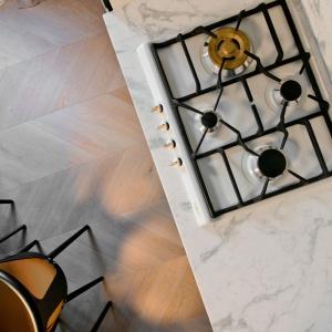 Dolne szafki kuchenne wieńczy piękny blat z prawdziwego marmuru, płynnie przechodzący w ścianę nad blatem. Projekt: Indre Sunklodiene. Fot. Leon Garbačauskas.