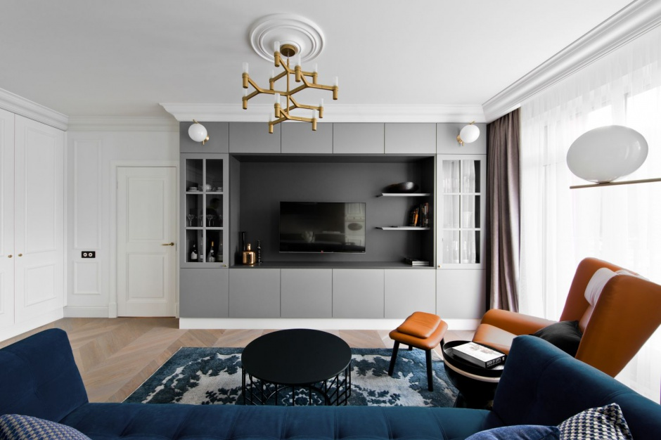 Nad salonem góruje i przyciąga wzrok piękna designerska lampa, która w swojej formie - tak jak cała strefa dzienna - jest trochę klasyczna, trochę nowoczesna. Projekt: Indre Sunklodiene. Fot. Leon Garbačauskas.
