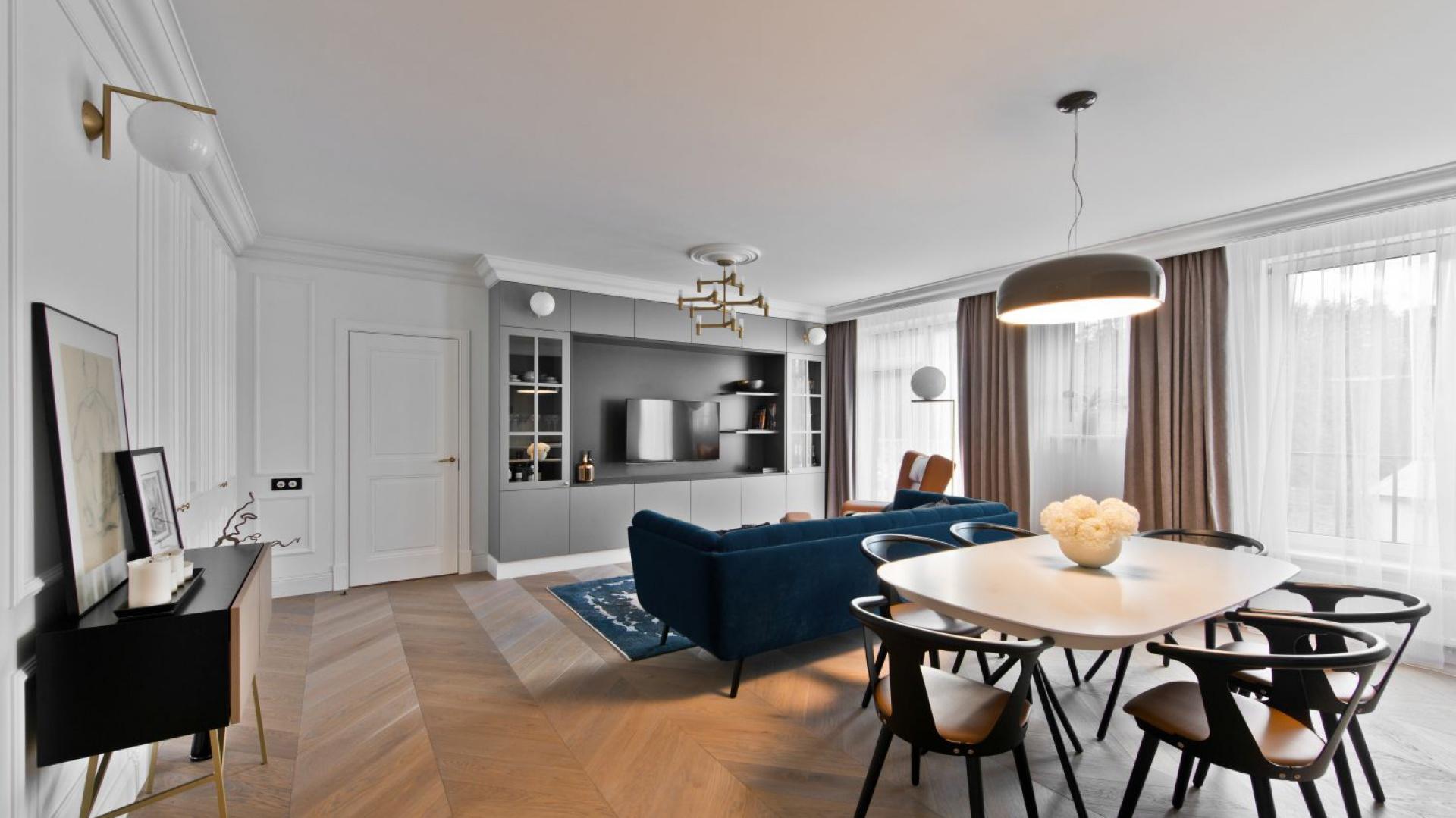 Naturalny parkiet ułożony w klasyczną francuską jodełkę ociepla wizualnie mieszkanie i wspólnie z ciężkimi zasłonami w oknach i aksamitną tapicerką kanapy nadaje mu przytulny charakter. Projekt: Indre Sunklodiene. Fot. Leon Garbačauskas.
