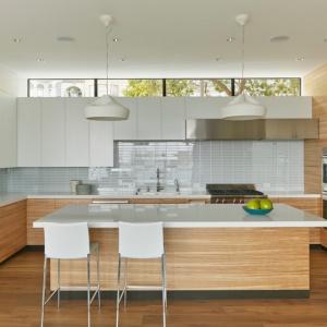 Nowoczesna kuchnia ujmuje gładkimi powierzchniami i czystymi liniami. Centrum pomieszczenia stanowi wyspa, ale pod ściana również poprowadzono długi funkcjonalny blat. Projekt: Studio Vara. Fot. Bruce Damonte.