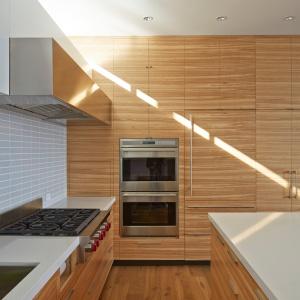 Górne szafki mają gładkie, matowe, białe fronty, a dolna i wysoka zabudowa wykończone zostały naturalnym fornirem, wybranym osobiście przez właściciela domu. Projekt: Studio Vara. Fot. Bruce Damonte.
