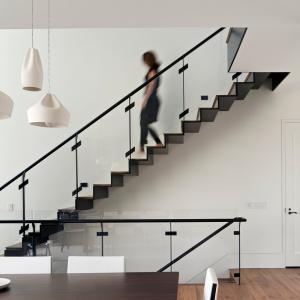 Czarne balustrady schodów i linie stopni oznaczają się efektownie na tle śnieżnobiałej ściany. Projekt: Studio Vara. Fot. Bruce Damonte.