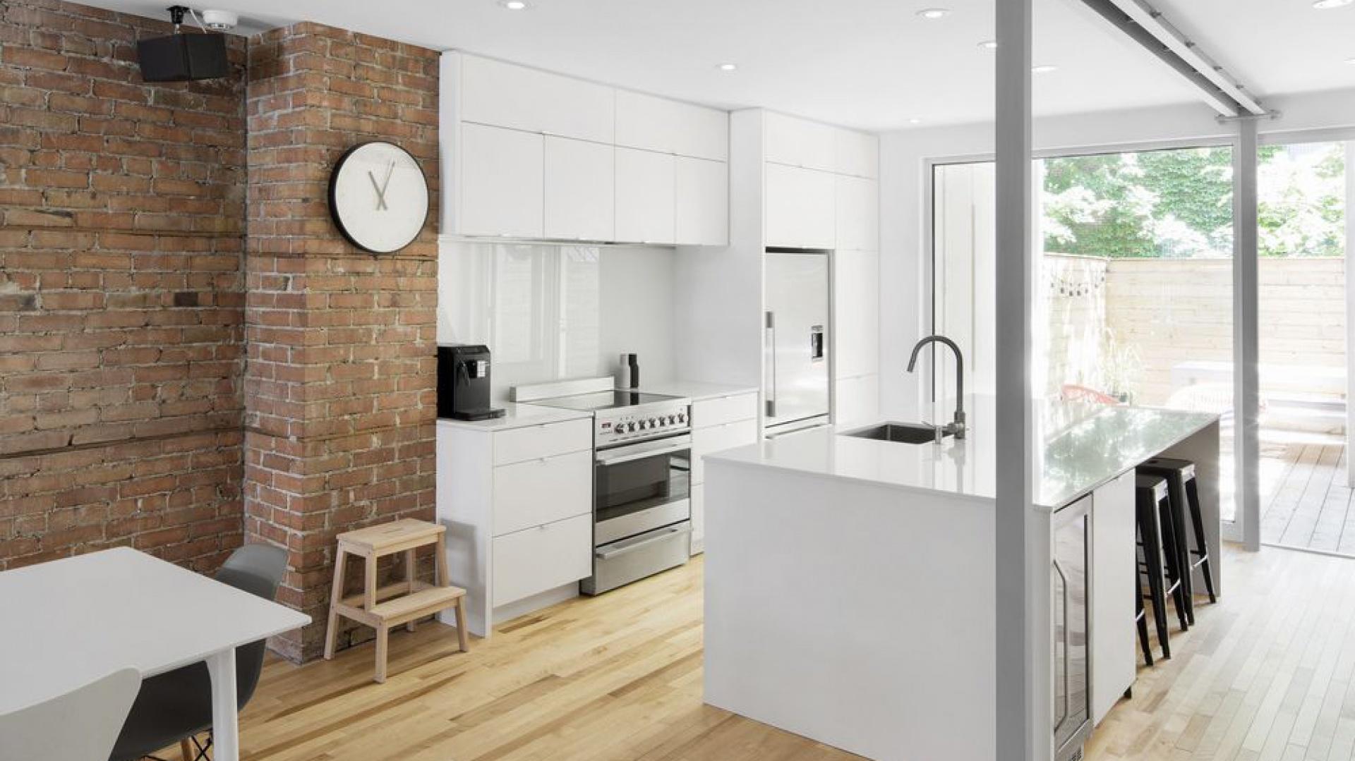 Biała, nowoczesna kuchnia z zabudową z lakierowanego MDF-u stanowi elegancki kontrast dla chropowatej, czerwonej cegły na ścianie. Projekt: Bourgeois / Lechasseur Architects. Fot. Adrien Williams.