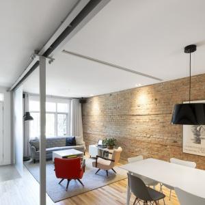Otwarta strefa dzienna obejmuje kuchnię, jadalnię oraz salon usytuowane w jednym rzędzie. Projekt: Bourgeois / Lechasseur Architects. Fot. Adrien Williams.