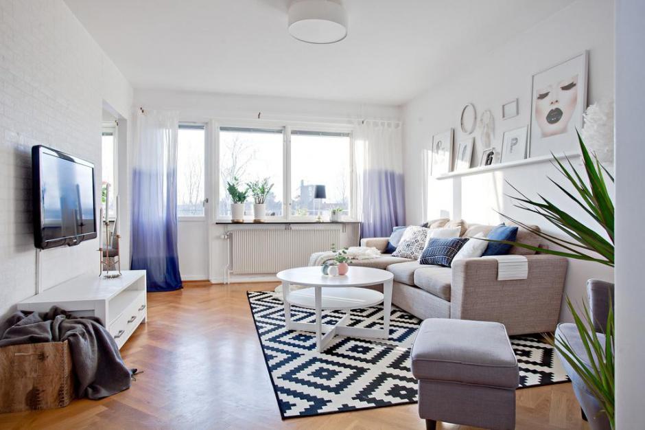Jasne kolory oraz gustowne dodatki. Tak można podsumować aranżację wnętrza tego mieszkania. Kompozycję bieli, błękitów i szarości ociepla drewniany parkiet ułożony w jodełkę. Fot. Svenskfast.se.